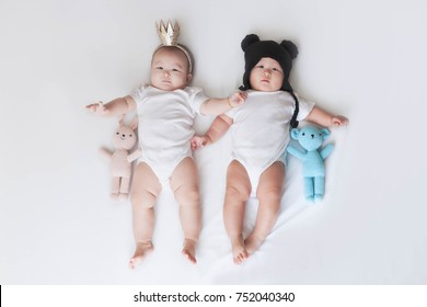 Cute twin babies boy and girl in white bodysuite with crown and winter hat. Asian twin babies.