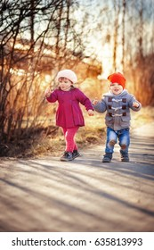 Cute twins boy and girl walk in park at sunset
