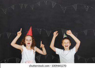 Cute twins kids with carnival hat at celebration birthday party. Happy mother, father day, and holiday concept.