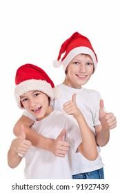 cute two kids in santa hats on white