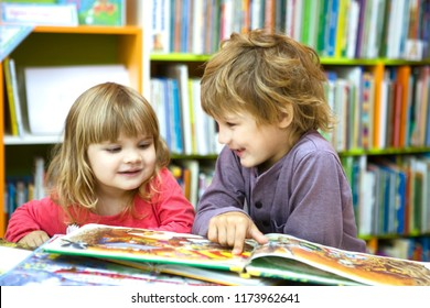 Cute two little kids, brother and sister  reading a book together in library