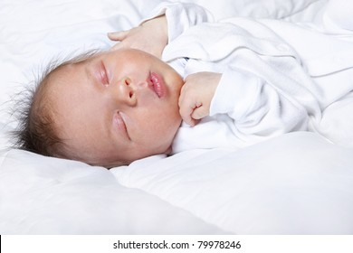 Cute two month baby sleeping on bed
