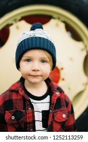 Cute two year old boy wearing a stocking cap in a winter or fall lifestyle portrait featuring the young kid in an image from a film scan.