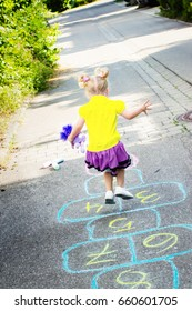Cute two years old girl playing hopscotch on the street, rear view
