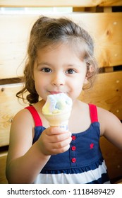 Cute two-year-old Lebanese-Caucasian girl enjoys an ice cream cone while sitting on a high backed pinewood bench. She takes a break from eating to look and smile at the camera. Red white blue shirt.
