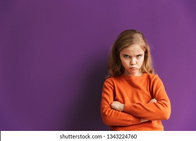 Cute upset little girl standing isolated over violet background, looking away