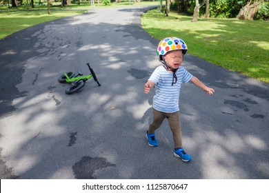 Cute upset stress sad unhappy little Asian 2 years old toddler baby boy child crying after fallen from his first bicycle / balance bike, Toddler's Terrible Twos and a child's tantrum in public concept