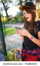 Cute urban girl in skate-park with skateboard using smart phone