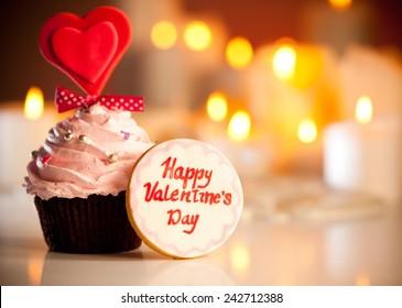 Cute Valentine's cookie with Happy valentine's day written on it next to Valentine's cupcake.
