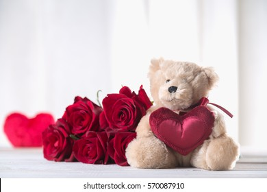 Cute valentine's teddy bear with red roses, love concept