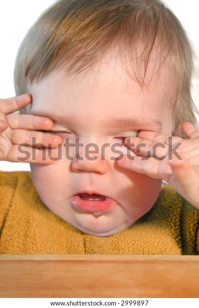 cute very tired baby rubbing eyes with his/her hands
