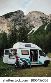 Cute vintage camper van or camping RV parked in wild camping spot in mountain forest. Bicycle off bike rack parked next to converted van. Life on the road in van, outdoor nomadic lifestyle