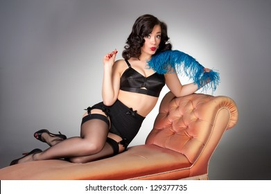cute vintage pinup seated on chaise