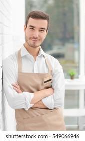 Cute waiter in beige apron on blurred background