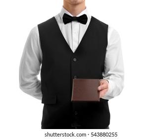 Cute waiter holding brown bill folder on white background