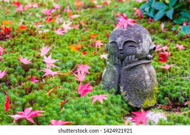Cute warabe jizo statue covered in fallen Japanese momiji maple leaves standing in the moss in the garden of Enkoji buddhist temple in Kyoto, Japan