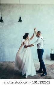 Cute wedding couple dancing at loft interior