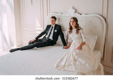 cute wedding couple in the interior of a classic studio decorated. hey kiss and hug each other