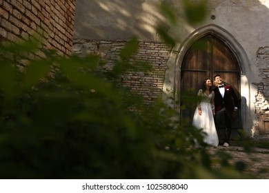 Cute wedding couple pose in front of old door and brick wall