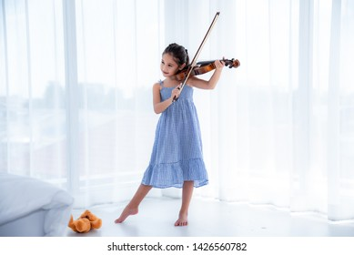 A cute white Asian girl wearing a blue skirt dress is playing a violin in a white background with sunlight.