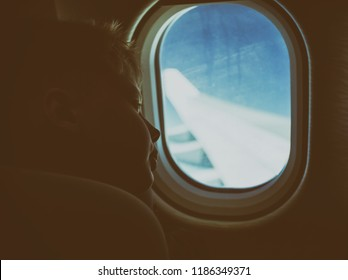 Cute white blond kid looking at window while sitting in his seat during flight. Color photography filtered in vintage style.