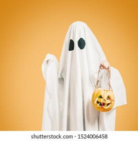 Cute white ghost with black eyes holding pumpkin basket with sweet candy on orange background.