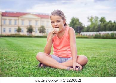 Cute white girl enjoying ice cream in the park