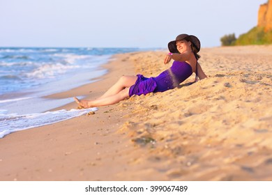 Cute white girl in hat and purple dress laying on sand