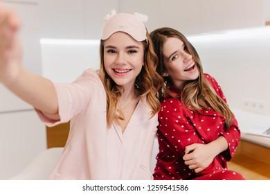Cute white girl with lovely smile making selfie in light room. Indoor shot of two amazing european ladies enjoying weekend.