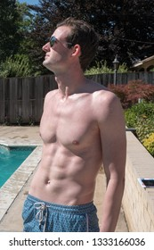 Cute white guy with defined abs with no shirt standing on a pool deck of an outdoor swimming pool in the summer sun. Sexy man with six pack abs in aviator sunglasses and swimming suit outside by pool.