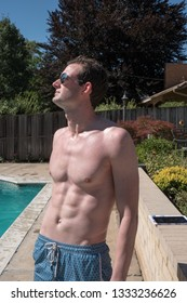 Cute white guy with defined abs with no shirt standing on the deck of an outdoor swimming pool in the summer sun. Sexy man with six pack abs in aviator sunglasses and swimming suit outside by pool.