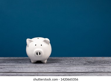Cute white Piggy Bank over a blue and grey background.