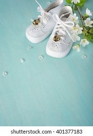 Cute, White Vintage Leather Infant Baby Shoes with spring flowers on Cyan Turquoise Faux Painted, Rustic wood Board Background with room or space for copy, text, your words. Vertical aerial side view