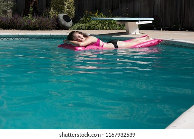 Cute white woman relaxing on a pink raft in a backyard swimming pool near a diving board on a sunny summer day.  Girl sunbathing on a raft in a swimming pool. Relaxation and getting away from it all.