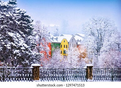Cute winter view, snowy weather, colorful traditional city houses peeking from behind naked trees and fence covered with snow in historical center of Innsbruck, Tyrol, western Austria