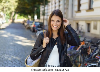 Cute woman adjusting hair while standing outside on old street with bicycle racks in background
