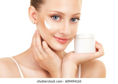 Cute woman applying cream to her face. Care for beautiful woman skin. Cosmetology, spa therapy and makeup at beauty salon. Closeup portrait of woman face with cream