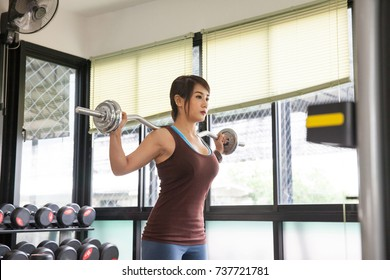 Cute woman with barbell flexing muscles in gym