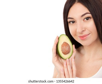 Cute woman with beautiful smile holding avocado. Healthy lifestyle and nutrition, dieting, weight loss, cosmetology, dental care and healthy teeth consept Close up portrait of beautiful woman isolated