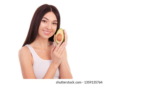 Cute woman with beautiful smile holding avocado. Healthy lifestyle and nutrition, dieting, weight loss, cosmetology, dental care and healthy teeth concept. Closeup portrait of beautiful woman in white