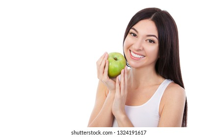 Cute woman with beautiful snow-white smile holding green apple. Nutrition, dieting, weight loss, cosmetology, dental care and healthy teeth concept. Close up portrait of beautiful woman