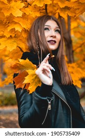 Cute woman in black clothes on a background of maple autumn leaves