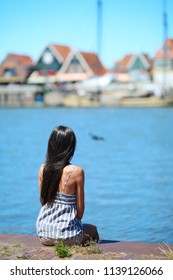 A cute woman brunette model with long hair sits with her back against a background of traditional Dutch houses. Fishing village, Volendam Netherlands.