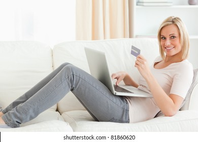 Cute woman buying on line while lying on a couch looking at the camera