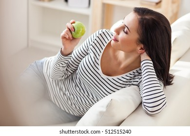 Cute woman enjoying apple at home