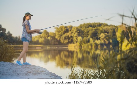 Cute woman is fishing with rod on the summer lake