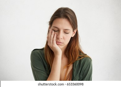 Cute woman having sleepy expression looking tired holding her hand on cheek closing her eyes with tiredness. Young woman having sad expression and toothache. People, problems, tiredness concept