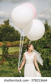 Cute woman holding big balloons on nature at sunny day