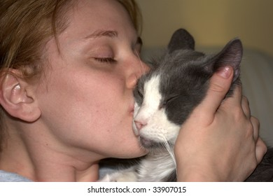 A cute woman kissing a cat