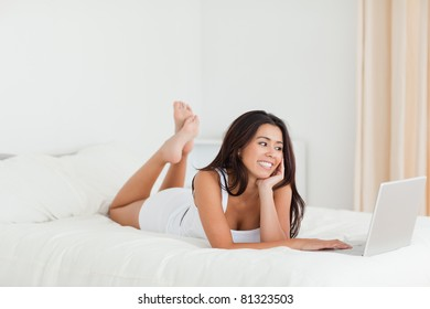 cute woman lying on bed with crossed legs looking at laptop in bedroom